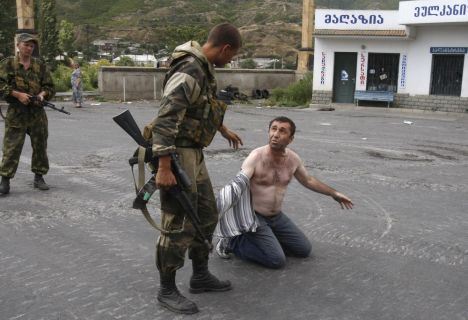Russian soldiers detain a man who carried a weapon in his car at a checkpoint in the Georgian city of Gori, near South Ossetia, in this August 14, 2008 file photo. Friday August 7, 2009 marks the first anniversary of the start of the conflict. REUTERS/Gleb Garanich/Files (GEORGIA CONFLICT MILITARY POLITICS)