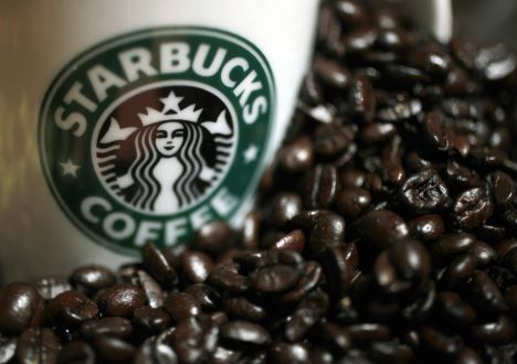 A mug bearing a Starbucks logo is pictured next to coffee beans during a news conference in Tokyo, in this file picture taken April 13, 2010. Japan's convenience store operators are jostling for eminence in a famously cut-throat industry, and one product has come up trumps for the market's top players - coffee. Millions and millions of cups of it. Inspired by a popular 100 yen ($0.93) blend launched by McDonald's in 2008, Seven-Eleven touched off a boom in convenience store coffee last year, lifting Japan's long-stagnant coffee market and rankling rival businesses. REUTERS/Yuriko Nakao/Files (JAPAN - Tags: BUSINESS)