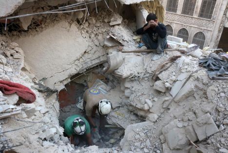 TOPSHOT - Syrian civil defence volunteers, known as the White Helmets, search for victims amid the rubble of destroyed buildings following a government forces air strike on the rebel-held neighbourhood of Bustan al-Basha in the northern city of Aleppo, on October 4, 2016. Assad's forces advanced on rebels during intense street fighting in the opposition-held east of Aleppo city, which Russia has been accused of bombing indiscriminately including targeting its hospitals. / AFP PHOTO / THAER MOHAMMED