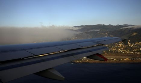 Smoke is seen from the window of an airplane landing at the airport of Funchal, in Madeira on July 20, 2012. Fires raged around the towns of Calheta, Ribeira Brava as well as in Santa Cruz, where one house was destroyed and a health centre, school and youth centre were evacuated as a precautionary measure. The problems started on July 18 evening when high temperatures and strong winds fanned a fire that broke out on the edge of the capital Funchal, gutting two houses and partially burning a third. AFP PHOTO / MIGUEL RIOPA